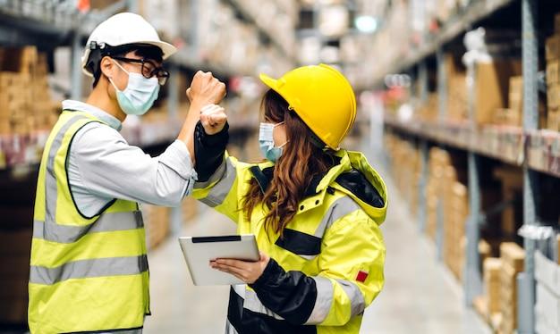 창고에있는 상품 배경이있는 선반에서 새로운 정상으로 팔꿈치로 떨리는 보호 마스크를 착용하는 코로나 바이러스에 대한 검역의 헬멧에 아시아 엔지니어 남녀