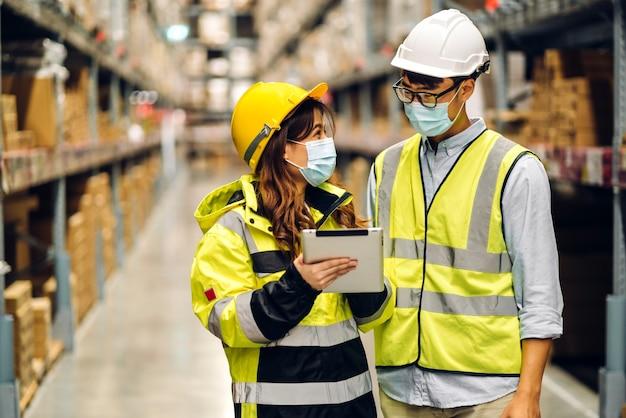Азиатский инженер мужчина и женщина в касках на карантине из-за коронавируса в защитной маске работают в новых нормальных условиях на полках с фоном товаров на складе. логистика и экспорт бизнеса