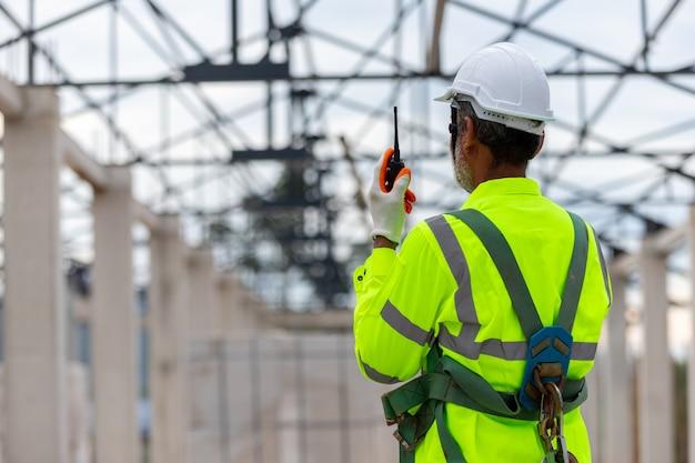 建設の屋根構造物の建設で建設管理を見ているアジアのエンジニア技術者