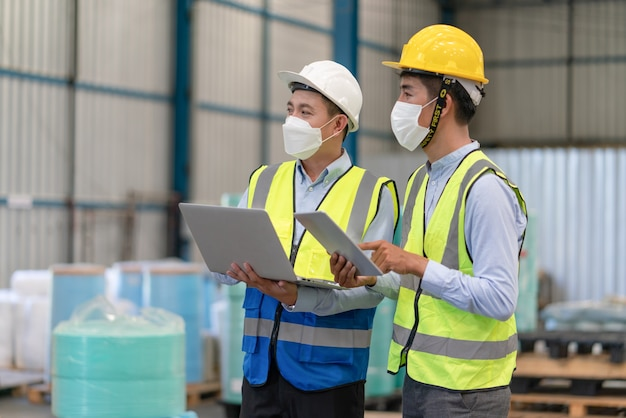 Asian engineer wear mask protect coronavirus use laptop talking with technician at warehouse factory