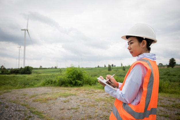 Asian engineer with hardhat using  tablet pc computer inspecting and working at wind turbine farm power generator station