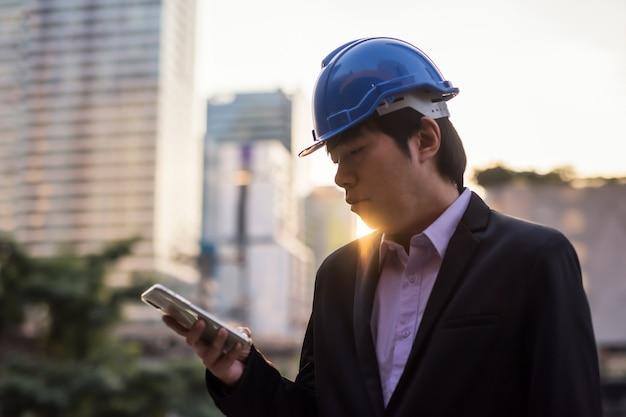スマートフォンを使用して安全ヘルメットを持つアジアのエンジニア