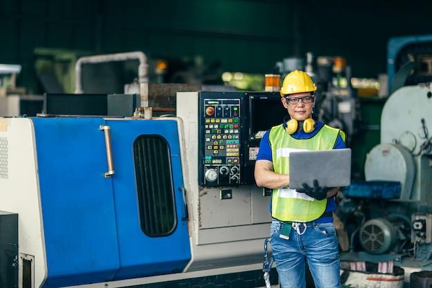 プログラムプロセスをセットアップするためにラップトップコンピューターで工場でマシンをプログラミングしているアジアのエンジニア