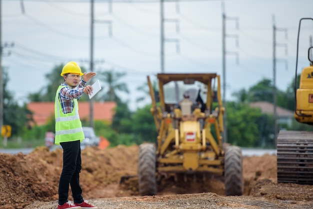 アジアのエンジニアは、道路の再建を監視し、建設現場で道路の建設を検査します。