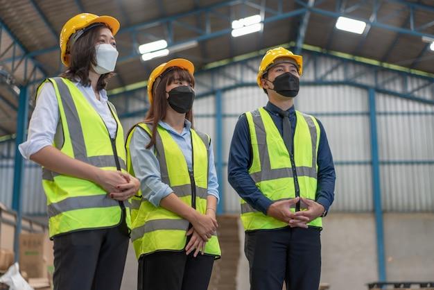 마스크를 쓰고 헬멧을 쓴 아시아 엔지니어들은 창고 공장에서 팀워크와 회의를 한다