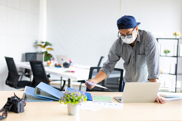 Азиатский предприниматель человек в маске занят работой на портативном компьютере, глядя на документ на бумаге в домашнем офисе.