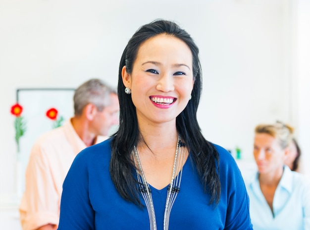 Asian ethnic woman smiling at the camera with two caucasians in the background.