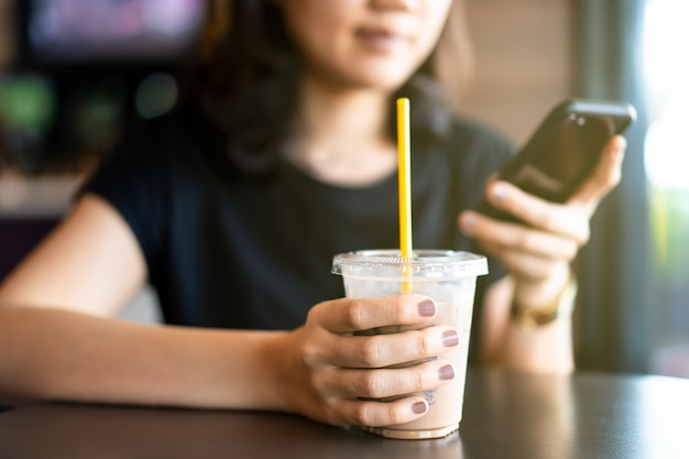 Asian ethnicity young woman relaxing and drinking iced coffee at coffee shop.