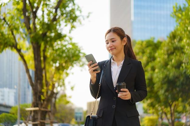 コーヒーカップを持って、タイのバンコクの背景にオフィスビルがある通りで携帯電話を使用しているアジアのエグゼクティブワーキングウーマン。