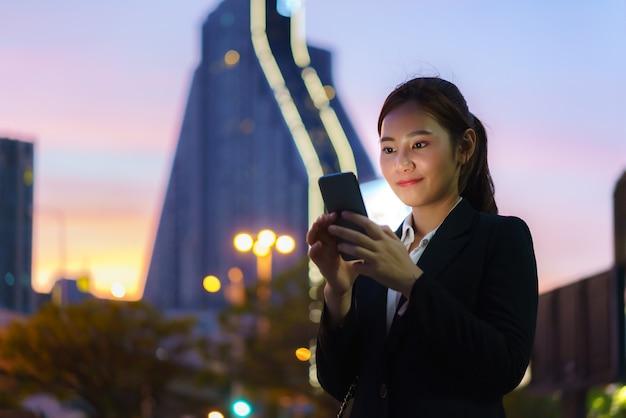 タイのバンコクで夜にオフィスビルを背景に通りで携帯電話を使用してアジアのエグゼクティブ働く女性。