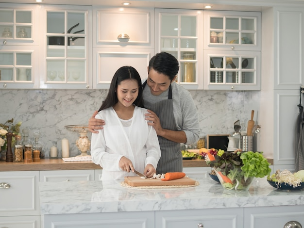 Asian expecting pregnant couple cooking together in the kitchen at home