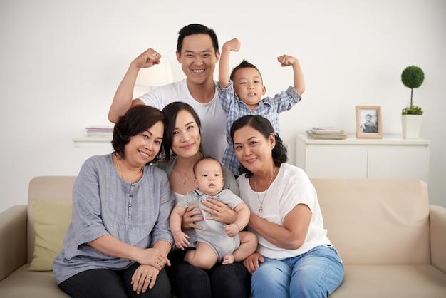 Азиатская расширенная семья с ребенком и малышом, позирующими вместе на диване у себя дома