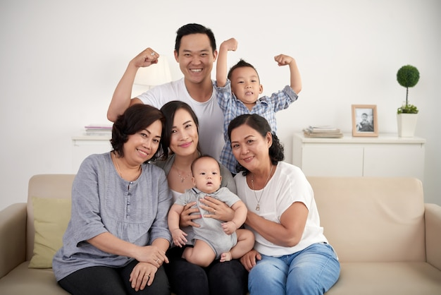 Asian extended family with baby and toddler posing together around couch at home