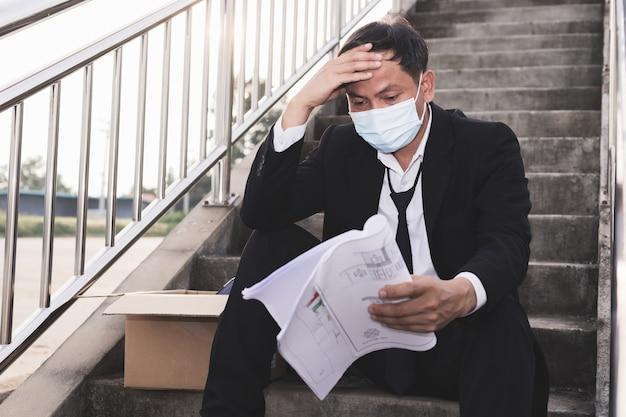 アジアの失敗失業者のビジネスマンは階段に座ってストレスを感じる
