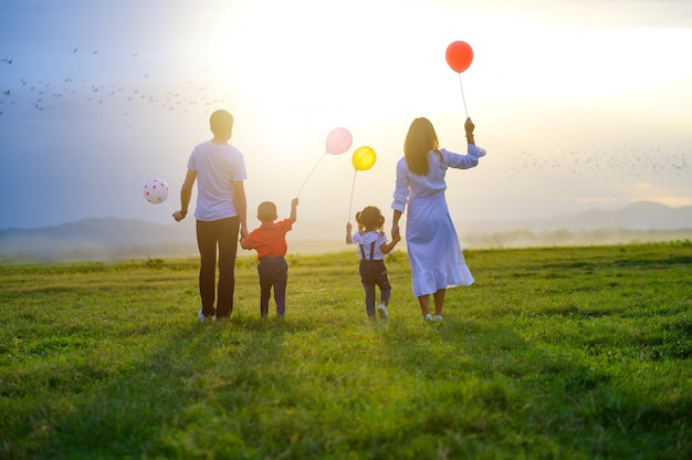 アジアの家族は日没の草原で幸せです。