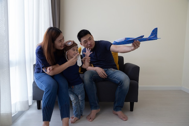 Asian family and 3 year old son having fun with toy plane and sitting on sofa in living room at home