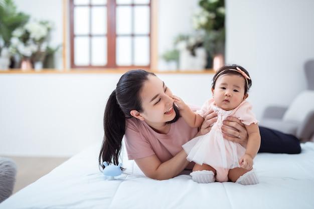 아시아 가족 및 모성 개념 집에서 작은 아기와 함께 행복 웃는 젊은 아시아 어머니