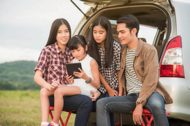 Asian family are happy sitting in the open trunk of a car