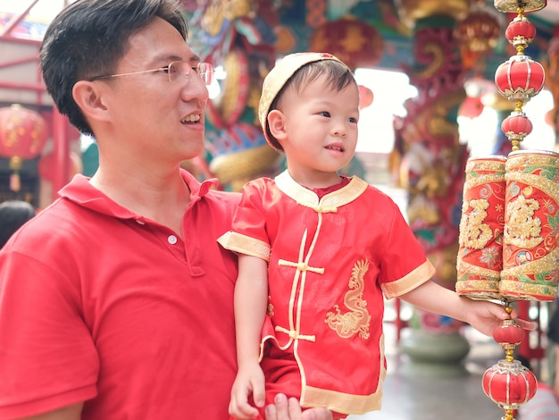 Asian family celebrating chinese new year, cute little 2 years old toddler boy child in traditional red chinese suit at local chinese temple with his father