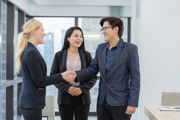 Asian family couple handshake with property real estate agent after made agreement home loan contract purchase of their