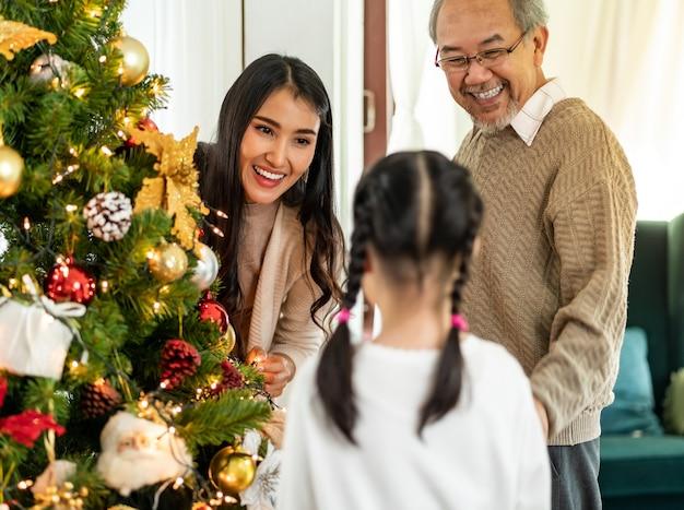 メリークリスマスの季節の挨拶のためにクリスマスツリーを飾るアジアの家族