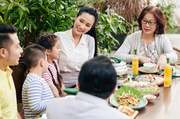 伝統的な料理を食べ、屋外の夕食のテーブルで話すアジアの家族