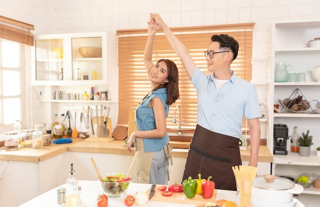 Asian family enjoy cooking salad and dancing together in kitchen room at home.