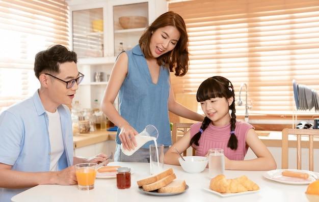 アジアの家族は自宅のキッチンルームで一緒に朝食を楽しんでいます。
