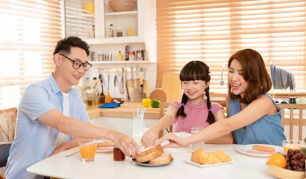 Asian family enjoy eating breakfast together in kitchen room at home.