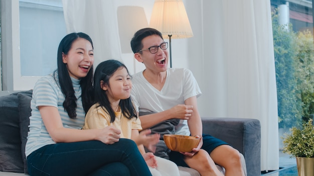 Asian family enjoy their free time relax together at home. lifestyle dad, mom and daughter watch tv together in living room in modern home at night .