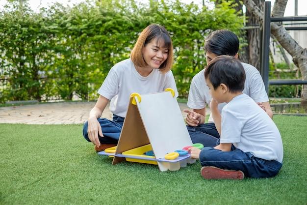 아시아 가족 아버지 어머니와 아들 집 정원에서 칠판을 가지고 노는. 어머니 이미지에 초점을 맞 춥니 다.