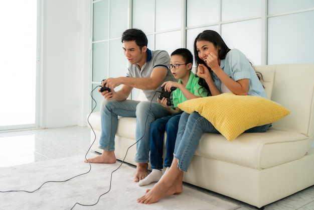 Asian family father and son having fun playing computer console games