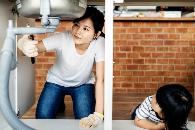 Asian family fixing kitchen sink