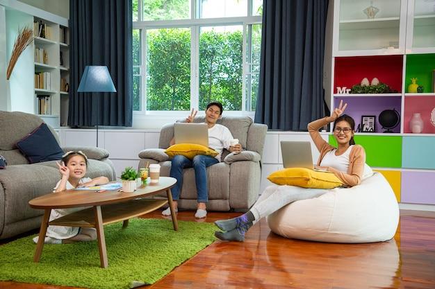 아시아 가족은 행복하고 집에서 일하기 위해 머물고 있습니다. 좋은 관계의 아버지와 어머니는 거실에서 함께 즐깁니다.