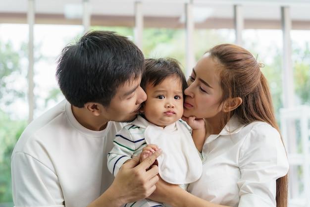 Азиатская семья счастливый поцелуй маленького мальчика в гостиной дома, молодые родители и дети наслаждаются любовным объятием, стоя вместе.