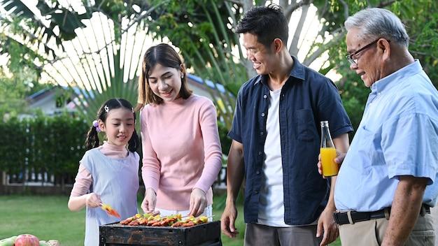 Азиатская семья, вечеринка с барбекю дома. готовим барбекю на гриле на заднем дворе. образ жизни на летних каникулах.