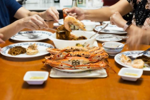 屋内で新鮮な蒸しワタリガニのシーフードと夕食をとるアジアの家族
