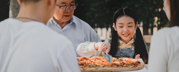 自宅の庭でピザを持っているアジアの家族。裏庭で子供と祖父のライフスタイルを持つ親。