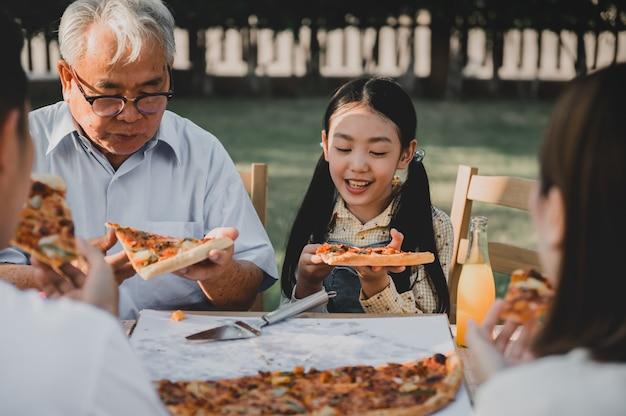집에서 정원에서 피자를 먹는 아시아 가족. 뒤뜰에서 아이와 할아버지 생활 방식을 가진 부모.
