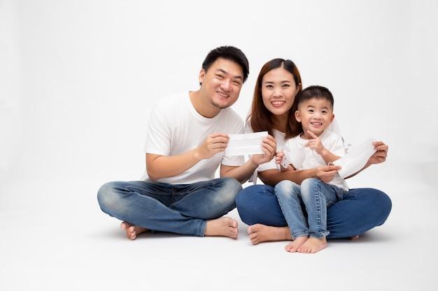 ウイルスを防ぐための防護マスクを保持しているアジアの家族