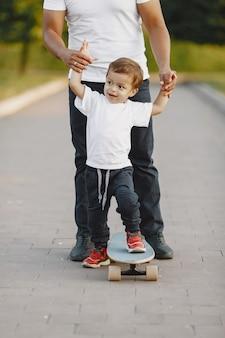 공원에서 아시아 가족. 흰색 t- 셔츠에있는 남자. 아버지는 아들에게 스케이트 타기를 가르칩니다.