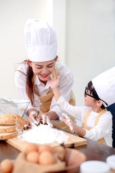 キッチンでアジアの家族。夏休みに健康的な料理を作るために息子を教えるお母さん。