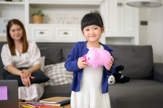 An asian family is teaching daughter on savings money with a piggy bank, financial planning concept
