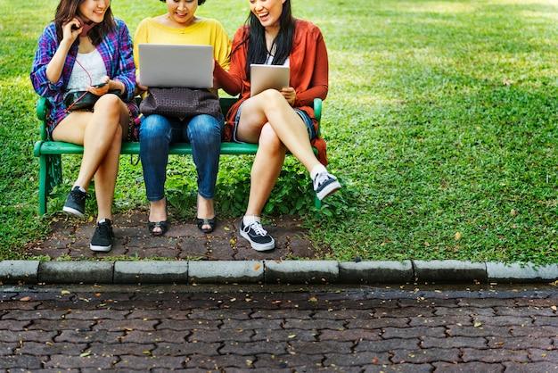 Азиатская семья использует цифровые устройства в парке
