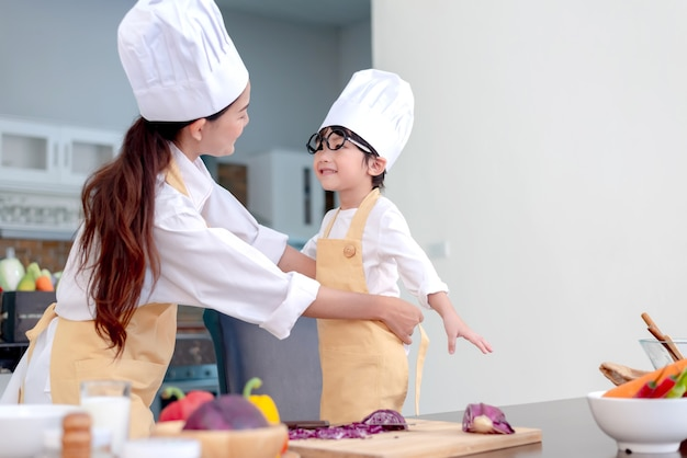 Asian family in the kitchen. mom teaching son for cook healthy food in summer holiday.