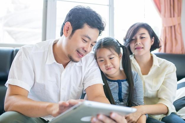 아시아 가족 라이프 스타일. 아버지, 어머니, 딸은 객실에서 함께 즐길 수 있는 태블릿을 시청합니다.