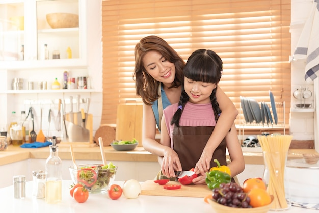 Asian family mom and child enjoy cooking salad together in kitchen room at home.