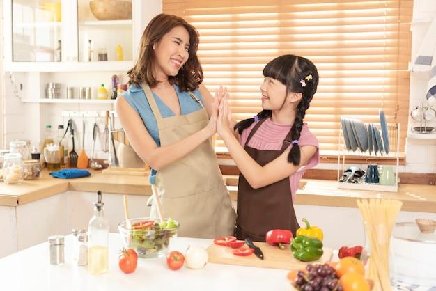 Азиатская семья, мать и дочь любят готовить, готовят салат вместе в кухонной комнате дома.