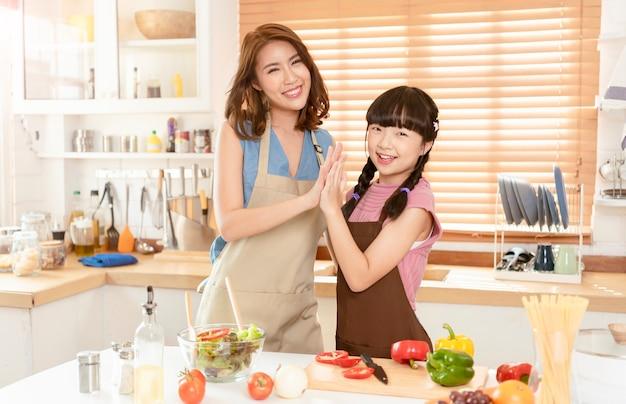アジアの家族、母と娘は自宅のキッチンルームで一緒にサラダ料理を準備する料理を楽しんでいます。