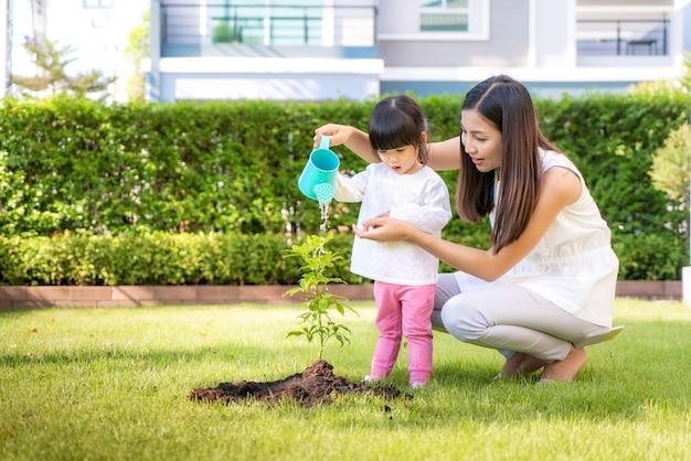 지구 온난화 성장 기능을 줄이고 자연 지구를 돌보기 위해 아시아 가족 어머니와 아이 딸 식물 묘목 나무와 자연 봄에 야외에서 물을주기.